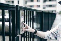 человек с бородой в светлой checkered куртке с клобуком в крышке и солнечных очках комплектует вверх номер квартиры на кнопочной  стоковое изображение rf