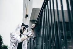 человек с бородой в светлой checkered куртке с клобуком в крышке и солнечных очках комплектует вверх номер квартиры на кнопочной  стоковые фото