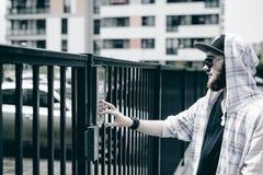 человек с бородой в светлой checkered куртке с клобуком в крышке и солнечных очках комплектует вверх номер квартиры на кнопочной  стоковое изображение