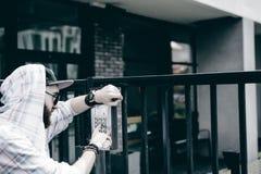 человек с бородой в светлой checkered куртке с клобуком в крышке и солнечных очках комплектует вверх номер квартиры на кнопочной  стоковое фото rf