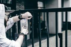 человек с бородой в светлой checkered куртке с клобуком в крышке и солнечных очках комплектует вверх номер квартиры на кнопочной  стоковые фотографии rf