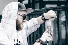 человек с бородой в светлой checkered куртке с клобуком в крышке и солнечных очках комплектует вверх номер квартиры на кнопочной  стоковые изображения