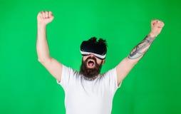 Человек с бородой в стеклах VR, зеленой предпосылкой Битник на крича повышении стороны вручает мощно пока взаимодействующий внутр стоковое изображение rf