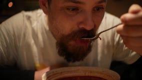 Человек с бородой есть борщ со сметаной суп Красно-свеклы Borsh сток-видео