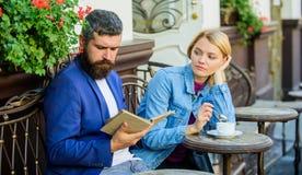 Человек с бородой и белокурая женщина на романтичной дате Общие интересы Пары в влюбленности сидят терраса кафа также датируйте ш стоковое фото rf