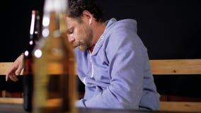 Человек с бородой и усиком сидит на таблице писать sms на его телефоне, и на таблице перед им 2 бутылки сток-видео