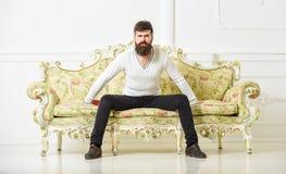 Человек с бородой и усиком тратит отдых с книгой Лектор сидит на софе и владения записывают, белая предпосылка стены self стоковые фотографии rf