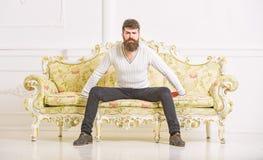 Человек с бородой и усиком тратит отдых с книгой Лектор сидит на софе и владения записывают, белая предпосылка стены self стоковая фотография rf