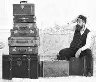 Человек с бородой и усиком упаковал багаж, белую внутреннюю предпосылку Мачо элегантное на утомленной стороне сидит, вымотанный н стоковые изображения