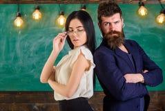 Человек с бородой и учитель в eyeglasses стоят спина к спине, доска на предпосылке Принципиальная схема сыгранности Учитель и Стоковое Изображение RF