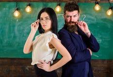 Человек с бородой и учитель в eyeglasses стоят спина к спине, доска на предпосылке Дама и битник работая совместно Стоковое Фото