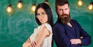 Человек с бородой и учитель в eyeglasses стоят спина к спине, доска на предпосылке Принципиальная схема сыгранности Дама и Стоковая Фотография