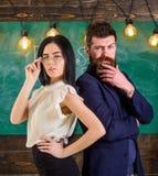 Человек с бородой и учитель в eyeglasses стоят спина к спине, доска на предпосылке Взгляд учителя и schoolmaster Стоковое Фото