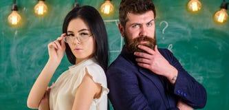 Человек с бородой и учитель в eyeglasses стоят спина к спине, доска на предпосылке Взгляд учителя и schoolmaster Стоковые Фото