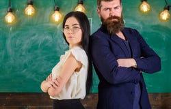 Человек с бородой и учитель в eyeglasses стоят спина к спине, доска на предпосылке Взгляд учителя и schoolmaster Стоковое Изображение