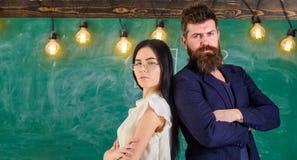 Человек с бородой и учитель в eyeglasses стоят спина к спине, доска на предпосылке Взгляд учителя и schoolmaster Стоковая Фотография