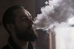 Человек с бородой и Mustages Vaping электронная сигарета Вапоризатор дыма битника Vaper и облако дыма Exhals стоковая фотография