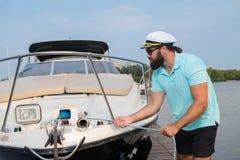 Человек с бородой пробует причалить его яхту стоковые фото