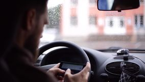 Человек с бородой сидит в автомобиле и пишет сообщение SMS на smartphone сток-видео