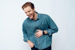 Человек с бородой смеясь над и держа животом стоковая фотография rf