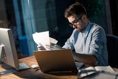 Человек с бумагами на компьтер-книжке Стоковое Изображение RF