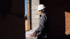 Человек с бумажным проектом в здании под конструкцией видеоматериал