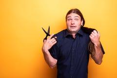 Человек с вспугнутым взглядом думая волос вырезывания с ножницами стоковые изображения rf