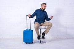 Человек с голубыми чемоданом и паспортом сидит на стуле около белой кирпичной стены стоковые фотографии rf