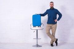 Человек с голубыми чемоданом и паспортом сидит на стуле около белой кирпичной стены стоковая фотография rf