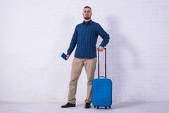 Человек с голубым чемоданом и паспорт около белой кирпичной стены стоковые изображения