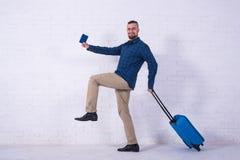 Человек с голубым чемоданом и паспорт около белой кирпичной стены стоковые фото