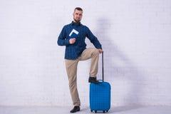 Человек с голубым чемоданом и паспорт около белой кирпичной стены стоковое изображение rf