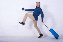 Человек с голубым чемоданом и паспорт около белой кирпичной стены стоковые фотографии rf