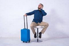 Человек с голубым чемоданом сидит на стуле около белой кирпичной стены и говорит на телефоне стоковые фото