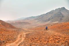 Человек с горным велосипедом в пустыне стоковая фотография rf