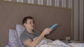 Человек с дистанционным управлением ТВ лежит на кровати сток-видео