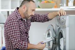 Человек с доской сзажимом для бумаги около стиральной машины стоковые фотографии rf
