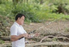 Человек с его рыбной ловлей штанги стоковое изображение rf