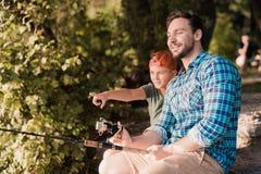Человек с его сыном сидит на речном береге и улавливает рыб Мальчик показывает ему что-то на реке стоковые фотографии rf