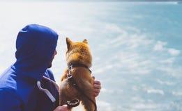 Человек с единением малой золотой японской собаки inu shiba сидя на горе и смотреть голубой горизонт моря, друзей дальше ослабляе Стоковое Фото