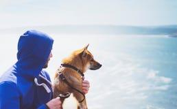 Человек с единением малой золотой японской собаки inu shiba сидя на горе и смотреть голубой горизонт моря, друзей дальше ослабляе Стоковые Фотографии RF