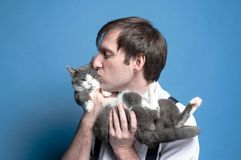 Человек с закрытыми глазами целуя и держа на заднем сером коте стоковые изображения