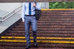 Человек с зонтиком вниз с метро на лестницах гранита стоковые изображения rf