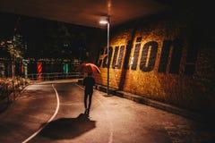 Человек с зонтиком идя на надпись дороги с осторожностью стоковые изображения