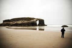 Человек с зонтиком на пляже. Стоковая Фотография RF