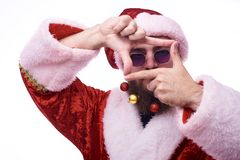 Человек с игрушками рождества в бороде и в костюме Санта Клауса держит руки перед его стороной в форме рамки стоковое фото rf