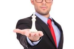 Человек с королем шахмат в ладони стоковое фото