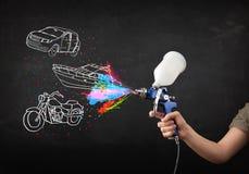 Человек с краской для пульверизатора airbrush с автомобилем, чертеж шлюпки и мотоцикла Стоковое фото RF