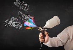Человек с краской для пульверизатора airbrush с автомобилем, чертеж шлюпки и мотоцикла Стоковые Фото