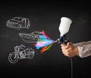 Человек с краской для пульверизатора airbrush с автомобилем, чертеж шлюпки и мотоцикла Стоковые Фотографии RF